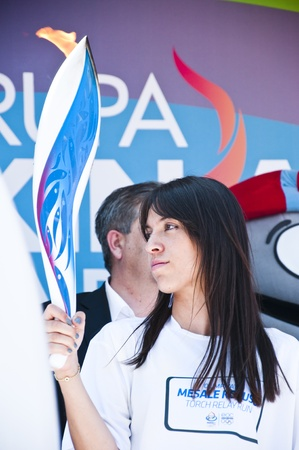 bearer: A beautiful young turkish girl holding the torch of 2011 trabzon youth olympic games, istanbul, turkey