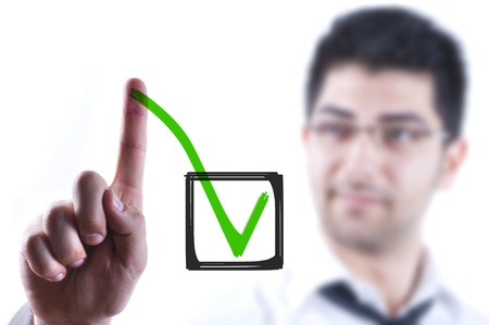 green board: Young business man drawing a tick in a box on a glass board Stock Photo