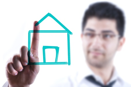 Young business man drawing a house on a glass board photo