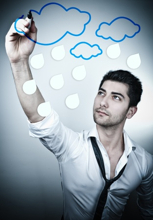 Young business man drawing rain clouds on a glass board photo
