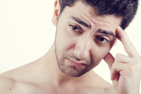 A worried young man thinking with his fingers on his forehead Stock Photo - 10100030