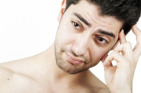A worried young man thinking with his fingers on his forehead Stock Photo - 10100028