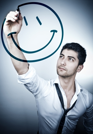 Young business man drawing a smiling face on a glass board photo