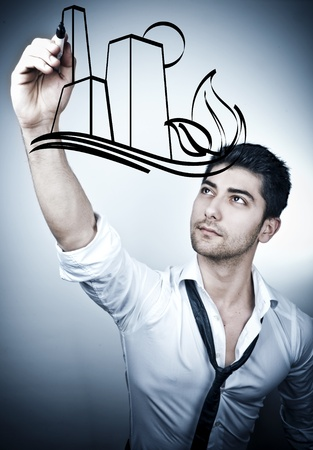 Young business man drawing a eco-friendly city on a glass board Stock Photo - 10100047