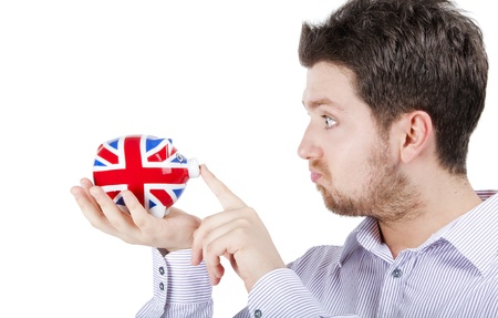 Isolated photograph of a blonde British man playing with a piggy bank with UK flag. Stock Photo - 10141665