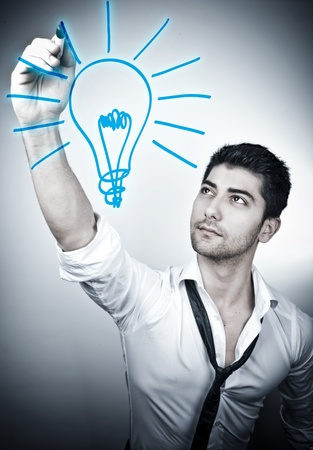 Young man drawing an idea bulb  Stock Photo - 10263500