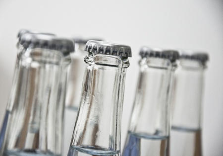 Full water bottles made of glass in a row photo