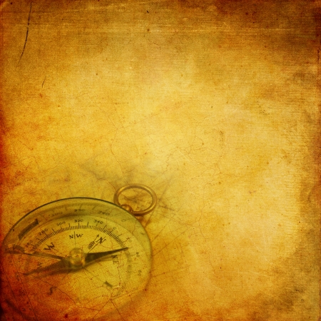 Aged paper background with an old compass and map pattern photo