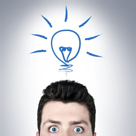 Young man surprised with wide open eyes and a bulb icon, brilliant idea concept photo