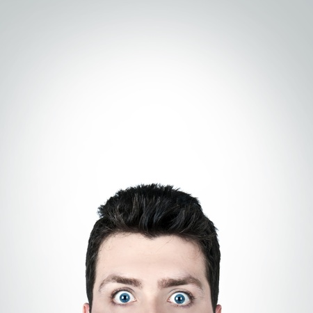 afraid man: Young man surprised with wide open eyes and copy space