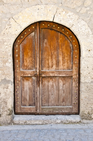 Old wooden door in a stone wall photo