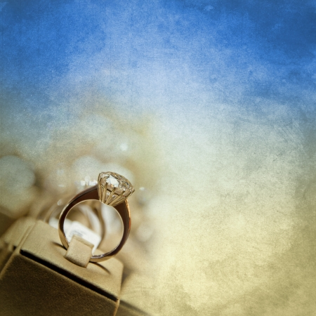 Diamond solitaire ring on old paper texture