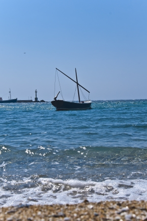 sun s: Single boat in the waters of the Aegean Sea