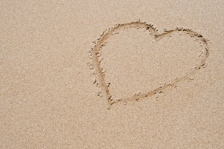 Heart drawn on sandy beach photo
