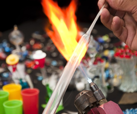 making a fire: Mans hand shaping glass with fire