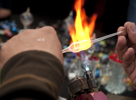 glassblower: Man s hand working on shaping glass, handcrafting