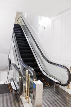bajando escaleras: Escalera móvil moderna en un interior escasa, con paredes blancas Editorial