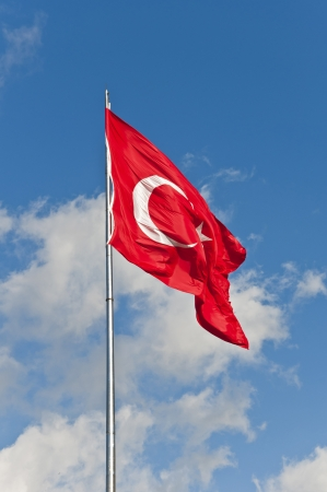 flagging: Large Turkish flag waving in the cloudy blue sky Stock Photo