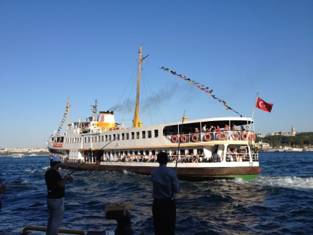 eminonu: Daily life in Istanbul with people fishing by the Bosporus and city line ferry