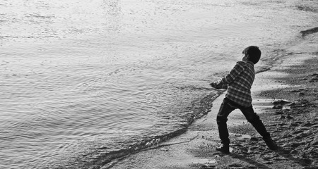 skipping: Kid skipping stones by the sea Stock Photo