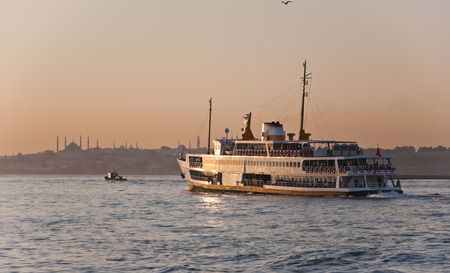 JAN 13 - ISTANBUL, TURKEY  Istanbul inner line steamboat heading from Asian side to the European in the sunset background, taken on January 13, 2014