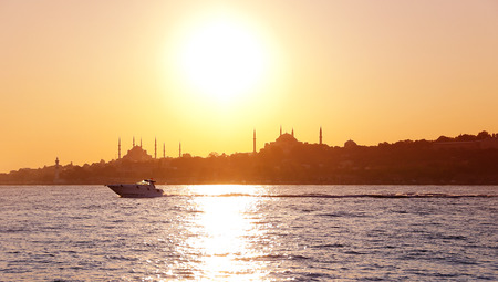 Beautiful sunset scene in Istanbul with orange sky and view of Hagia Sophia and Blue Mosque photo
