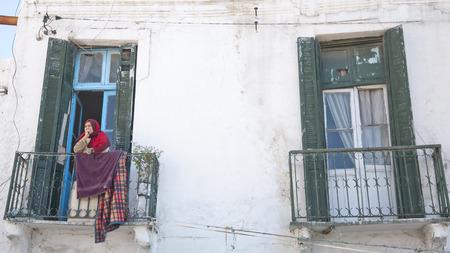 Tunis - February 24, 2014  Portrait of an old Tunisian lady looking around on her balcony in La Medina, the center district of Tunis city, Tunisia on Feb 24, 2014
