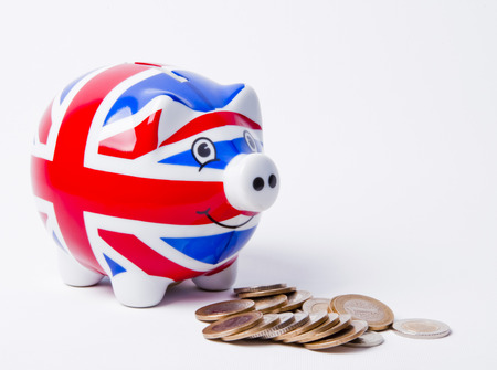 Piggy bank with British flag and coins