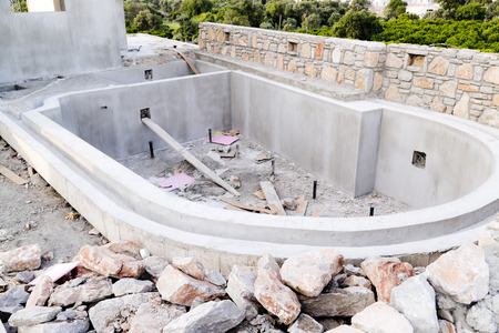 Swimming pool in a residential building under construction, raw cement and natural rocks