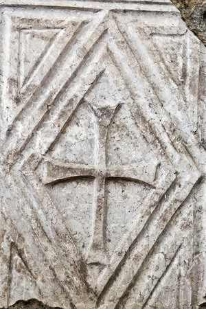 urban decay: Ancient cross carved on stone Stock Photo