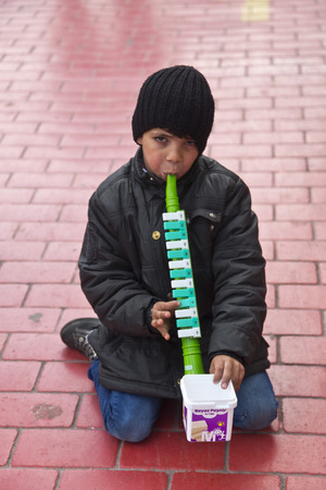 kadikoy: ISTANBUL, TURKEY - MARCH 9, 2014 : Little kid playing a plastic flute in the street, collecting money from people walking by. Working kids issue is an important problem in Istanbul, taken on March 9 Editorial