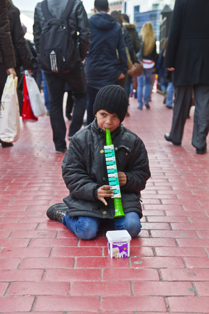ISTANBUL, TURKEY - MARCH 9, 2014 : Little kid playing a plastic flute in the street, collecting money from people walking by. Working kids issue is an important problem in Istanbul, taken on March 9