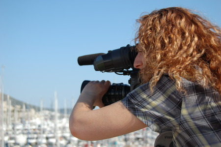 outside shooting: Young female cameraman at video shooting outside in Bodrum, Turkey