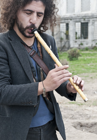 oudoors: ISTANBUL, TURKEY - MARCH 15, 2014: Street musician playing Ney, a traditional Turkish-Islamic musical instrument in Sultanahmet Square, Istanbul on March 15 Editorial