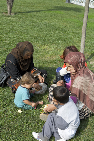 Istanbul, Turkey - August 14, 2016: Syrian refugee family sitting at a park in Istanbul. Millions of Syrians fleed to Turkey during the war in Syria.