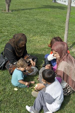 Istanbul, Turkije - 14 augustus 2016: Syrische vluchtelingenfamilie die in een park in Istanbul zit. Miljoenen Syriërs vliegen naar Turkije tijdens de oorlog in Syrië.