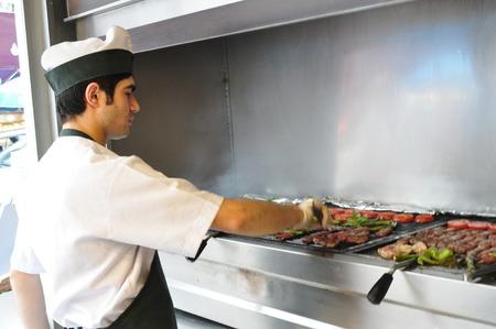 turkish bread: A Turkish chef making traditional Turkish kebabs on grill