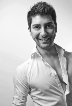Young man with white shirt, happy expression with a slight smile on his face, black and white studio portrait photo