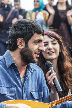 saz: Kurdish people living in Turkey singing and dancing on a marching day in Kadikoy district of Istanbul. Editorial