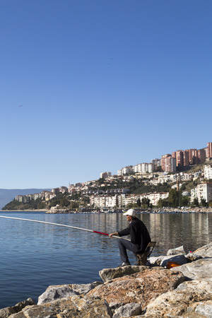 marmara: Gemlik Turkey  May 20 2015: Unidentified man fishing by the coast of Marmara Sea Gemlik Bursa southwest of Turkey on May 20.