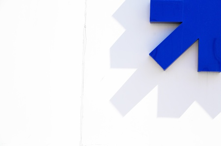 urban: Abstract minimal concept with blue arrow on white wall