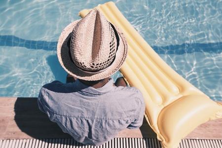 man: Man sitting by the pool