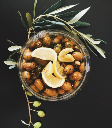 black: Freshly seasoned olives in a glass bowl and olive branches around it