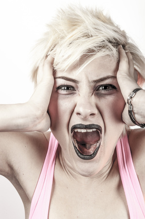 Young girl with short blonde hair and black lipstick screaming, negative facial expression and gesture, studio portrait