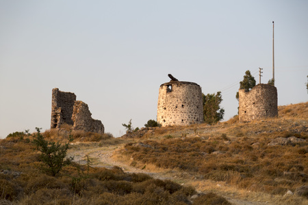 Sunset scene at the ruins of the historical Aegean stone windmills in Ortakent, Bodrum located in southwest Turkey.