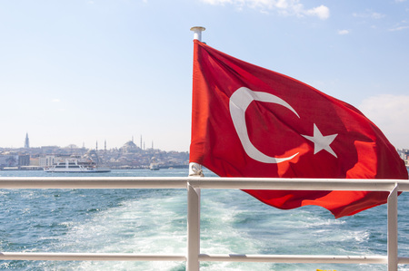 Istanbul city silhouette and Turkish flag from a boat on the Bosphorus, Turkey