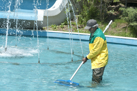 ISTANBUL, TURKEY - MAY 28, 2014: Municipal worker cleaning the decorative pool and fountains inside the public Macka Park in Istanbul on May 28, 2014
