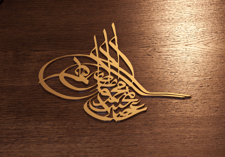 Ottoman tughra, brass relief on wooden background Stock Photo