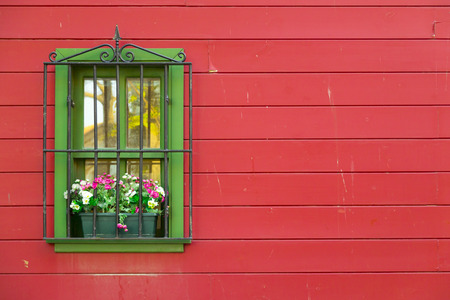 saturated color: Shabby green window on a red wooden wall, architectural detail
