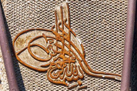 the merciful: Rusty metal Ottoman Tughra shaped islamic basmalah. Meaning; In the name of God, most graceful, most merciful.
